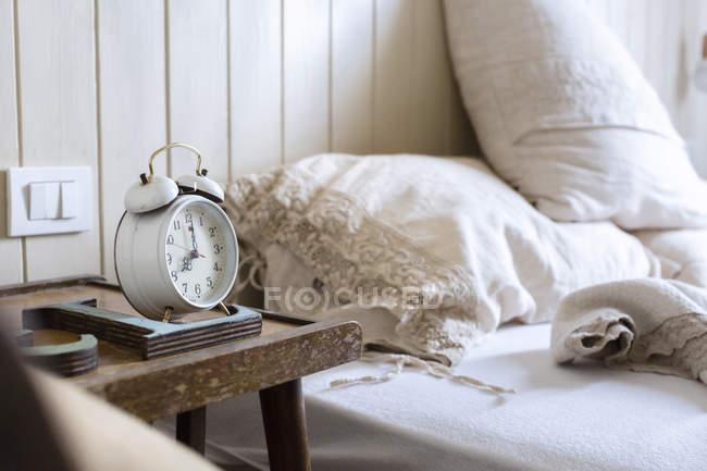 Cama desfeita, o despertador na mesa de cabeceira — Fotografia de Stock