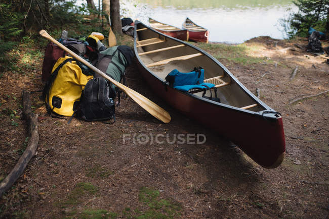 Canoe and camping equipment beside lake — Stock Photo