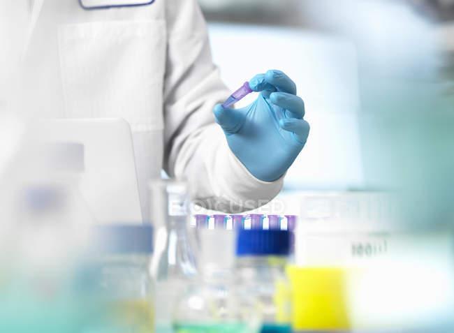 Image recadrée du savant détenant échantillon dans le flacon d'endorphine au cours de l'expérimentation en laboratoire — Photo de stock