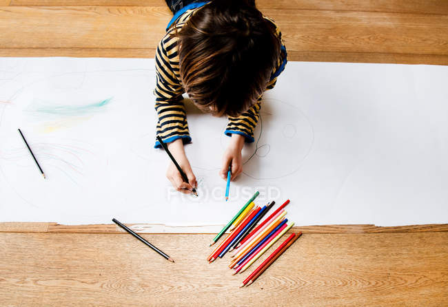 Overhead view of boy lying on floor drawing on long paper — Stock Photo