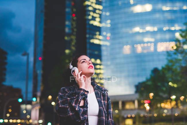 Donna con le cuffie in città guardando in alto, Milano Italia — Foto stock