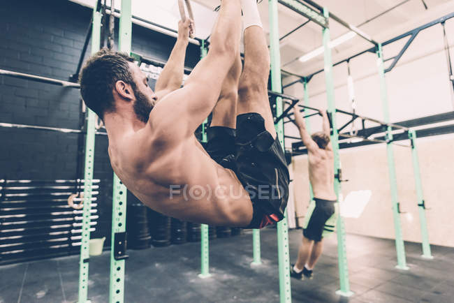 Young male cross trainer training on exercise rings in gym — Stock Photo