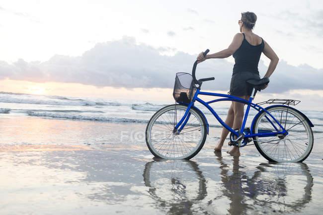 Жінка з велосипеда виглядає зі пляжі на захід сонця, Nosara, Ґуанакасте провінція, Коста-Ріка — стокове фото