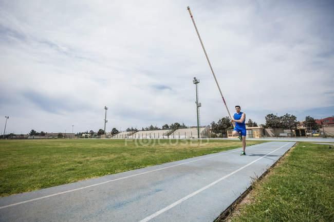 Молоді чоловіки рекордсмен спрінт з жердиною на спорт об'єкта — стокове фото