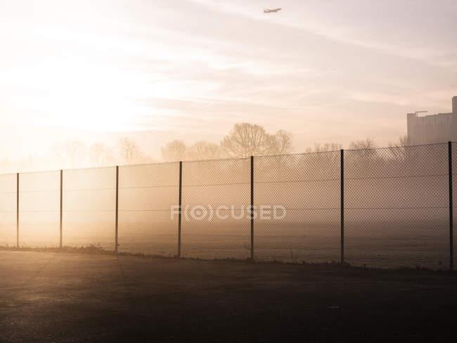 Теннисный корт ограда и воздушный самолет над головой в туманном парке на рассвете — стоковое фото