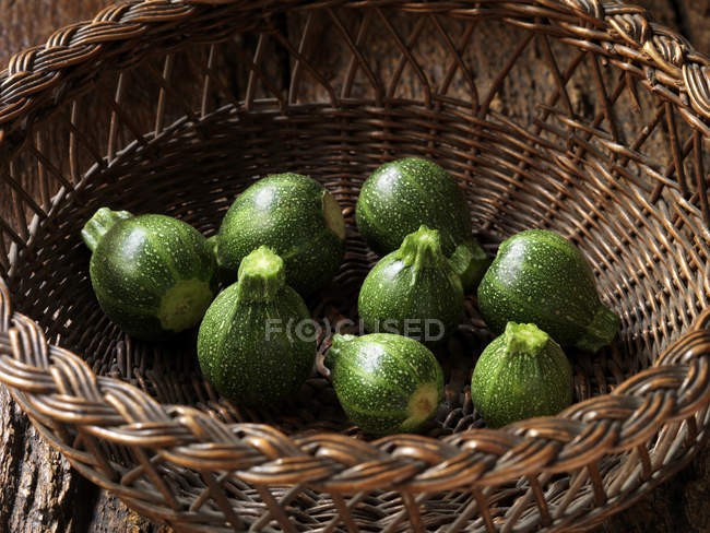 Fresh organic vegetables, baby round courgettes in basket — Stock Photo