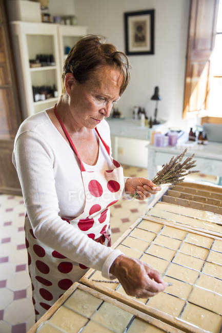 Mature woman applying dried lavender to soap bars in handmade soap workshop — Stock Photo
