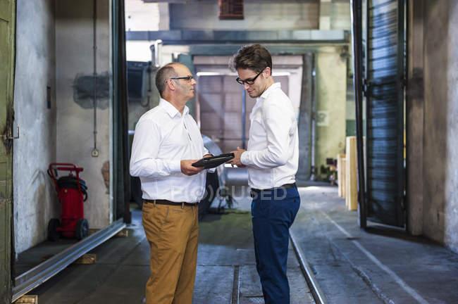 Deux ouvriers masculins ayant la discussion dans l'usine de rouleau en caoutchouc — Photo de stock