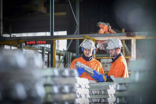 Workers in protective workwear inspecting aluminium ingot in foundry — Stock Photo