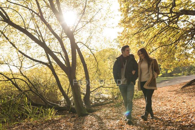Jeune couple marchant en forêt, bras dans le bras, souriant — Photo de stock