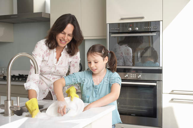 Mother and daughter washing dishes — Stock Photo