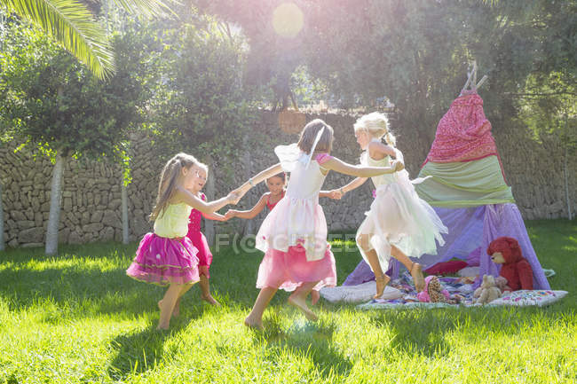 Five girls in fairy costumes playing in garden — Stock Photo