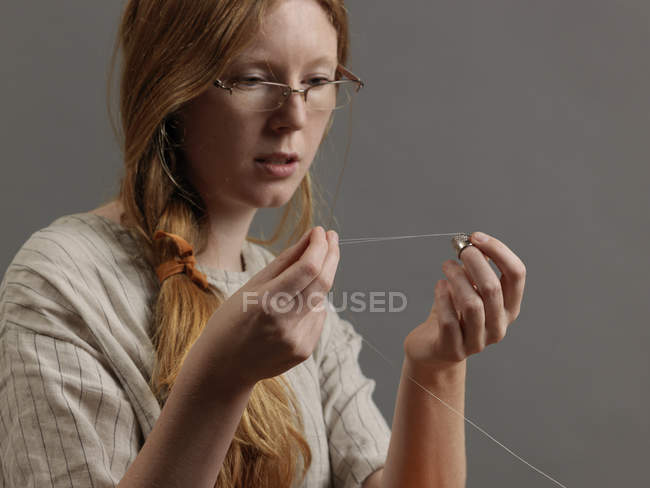 Young female designer threading a sewing needle — Stock Photo