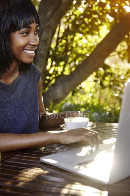Young woman sitting outdoors, using laptop, drinking coffee — Stock Photo