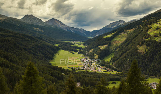 Landscape view of mountains and village under cloudy sky — Stock Photo
