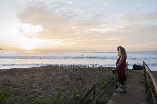 Mulheres desfrutando do pôr do sol na praia — Fotografia de Stock
