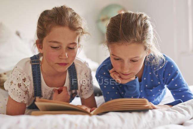 Две сестры, лежащие на кровати и читающие книгу — стоковое фото