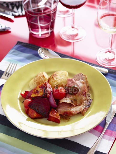 Cordeiro assado e pato com batatas no prato — Fotografia de Stock