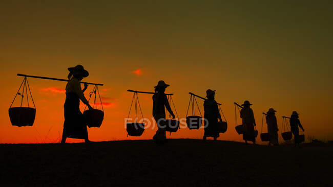 Silhouette of workers carrying yoke and buckets at sunset, Myanmar. - foto de stock