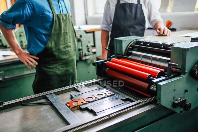 Artisan/technicien supérieur superviser le jeune homme sur la machine de la typographie dans l'atelier d'arts de livre, section — Photo de stock