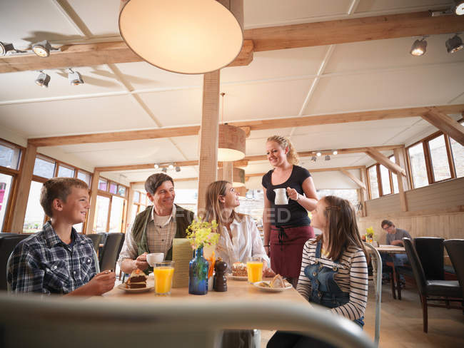 Waitress serving family meal in farm shop cafe — Stock Photo