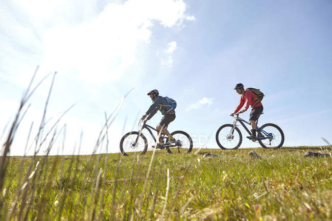 Side view of cyclists cycling on hillside — Stock Photo