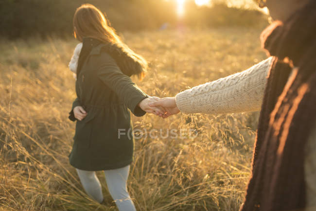 Junges Paar geht bei Sonnenuntergang durch Feld — Stockfoto