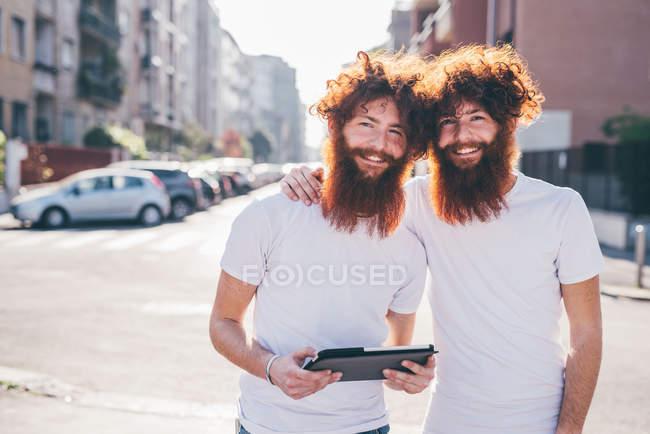 Портрет молодых хипстерских близнецов с рыжими волосами и бородами на городской улице — стоковое фото