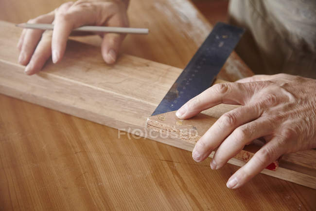 Hands of male carpenter using set square at workbench — Stock Photo