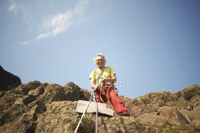 Vue en angle bas du grimpeur tenant une corde d'escalade regardant la caméra sourire — Photo de stock