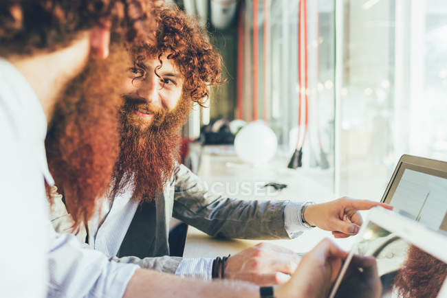 Male adult hipster twins pointing at laptop in office — Stock Photo