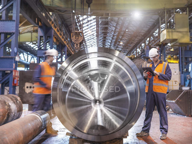 Engineers checking steel part in engineering factory — Stock Photo