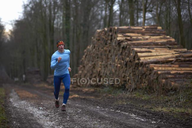 Вид бегуна в полный рост, бегущего по древесной дорожке стопкой бревен — стоковое фото