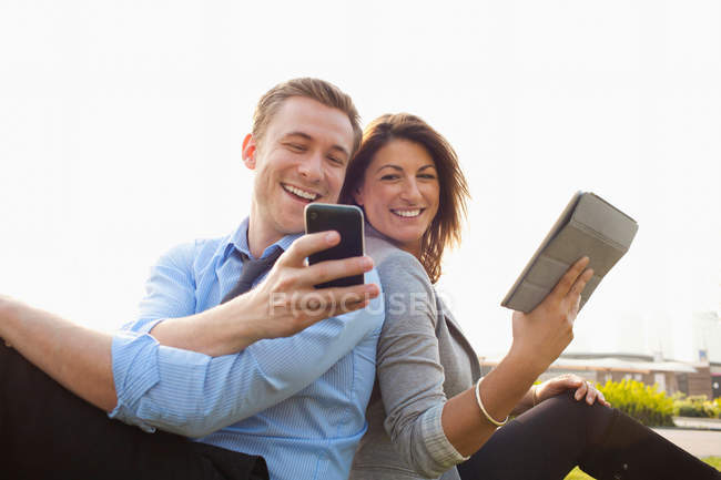 Couple using smart phone and digital tablet — Stockfoto