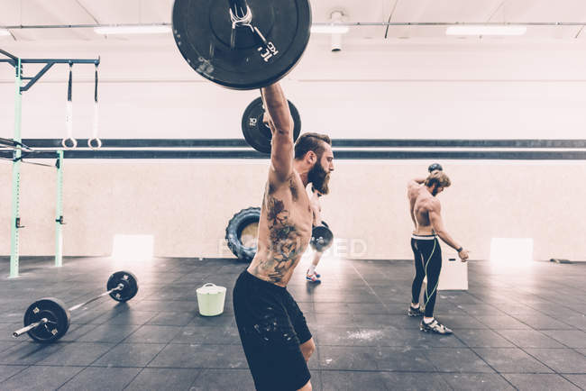 Young male cross trainer snatch lifting barbell in gym — Stock Photo