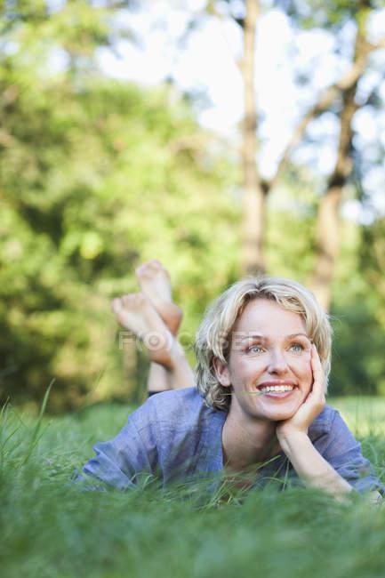 Жінка, що лежить в траві посміхається — стокове фото