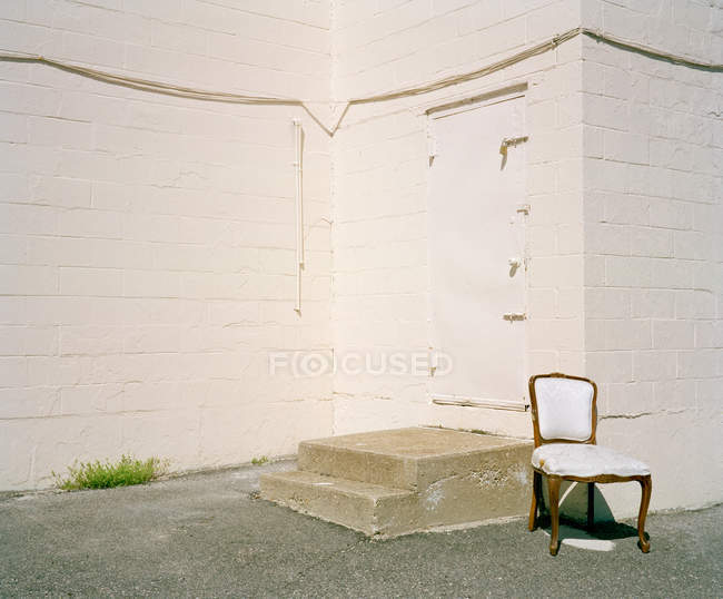 Empty chair outside closed door — Stock Photo