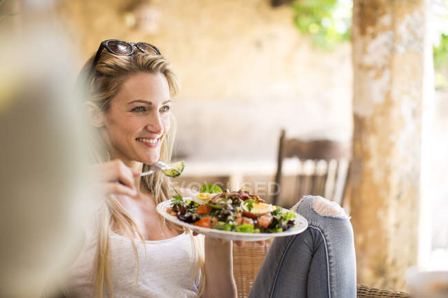 Young woman relaxing on garden patio eating salad — Stock Photo