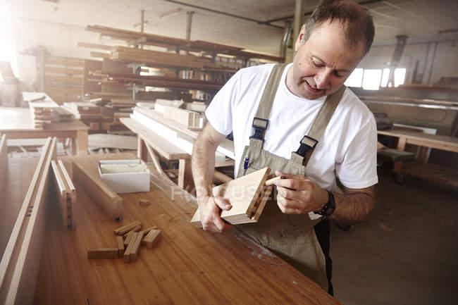 Mann schreinert Holzdübel an Werkbank ein — Stockfoto