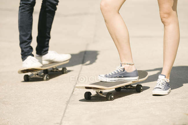Legs of female and male skateboarders standing in skatepark — Stock Photo