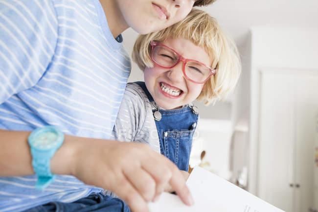 Девушка корчит рожи во время чтения с братом на кухне — стоковое фото