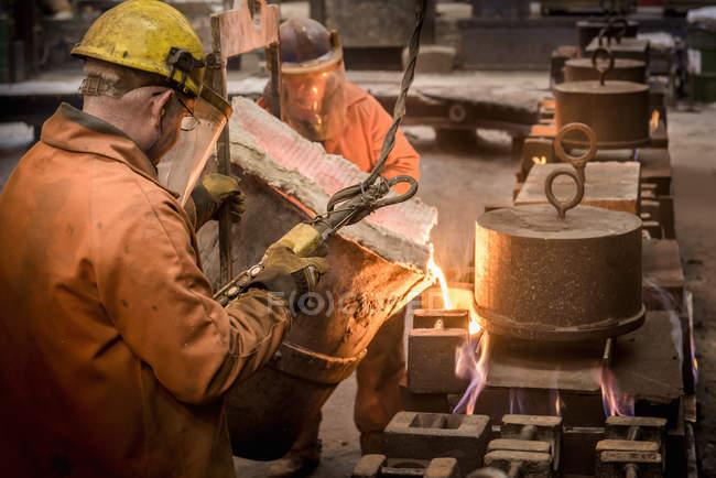 Lavoratori che versano metallo fuso dal pallone in fonderia — Foto stock