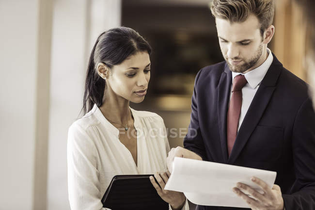 Young businessman and woman reading paperwork in office — Stock Photo