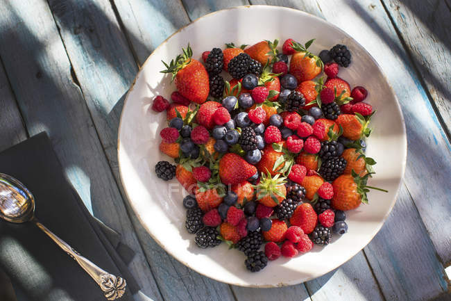 Plate of fresh, mixed berries on wooden surface, top view — Stock Photo