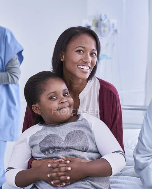 Портрет девочки-пациента, сидящей на коленях у матери в больничном детском отделении — стоковое фото