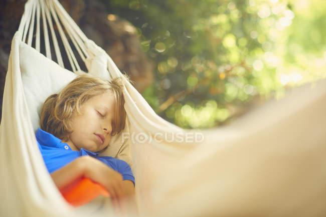 Cute boy reclining in garden hammock asleep — Stock Photo