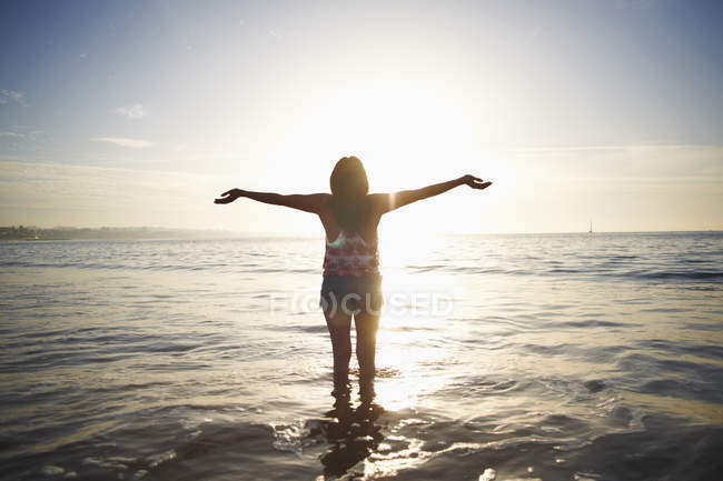 Rear view of woman standing in sea with arms open, Cascais, Portugal — Stock Photo