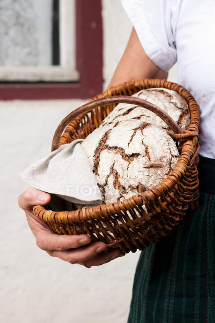 Woman holding basket of sourdough bread — Stock Photo