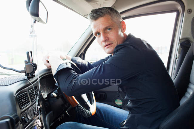 Taxi driver sitting at steering wheel — Stock Photo