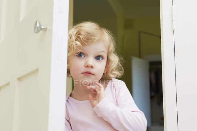 Female toddler peering from door — Stock Photo